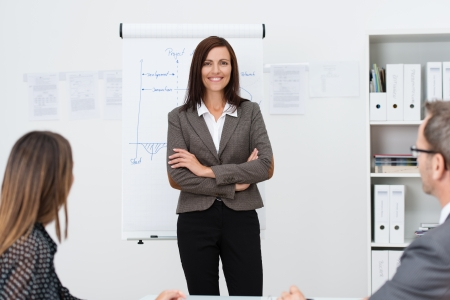 Confident businesswoman giving a presentation to her colleagues standing facing them in front of a with her arms folded photo