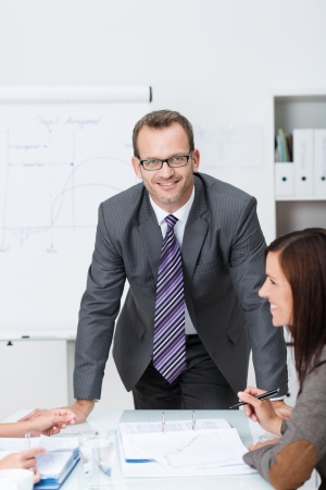 Confident friendly business manager or corporate executive standing leaning on a table at a meeting with colleagues, looking at the camera with a smile photo