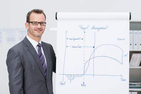Smiling confident stylish young male project manager in glasses giving a presentation standing alongside a flipchart with an analytical graph photo