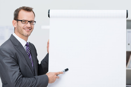marker pen: Smiling businessman giving a presentation pointing with his marker pen to a blank flipchart with copyspace for your text