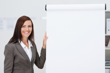 Confident happy businesswoman doing a presentation standing alongside a blank flipchart with white paper and copyspace for your text photo