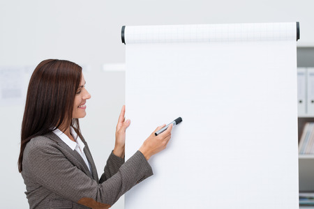 Smiling businessman pointing to a blank flipchart with copyspace for your text as she does a business presentation in the office photo