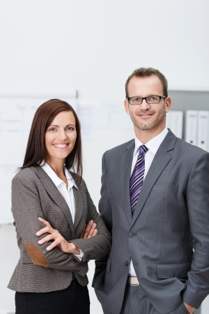 Stylish confident business team with an attractive man and woman standing side by side in the office looking at the camera with friendly smiles photo
