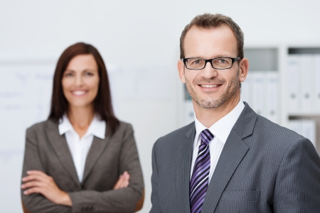 Handsome confident businessman in glasses standing facing the camera with a friendly smile with an attractive female coworker in the background photo