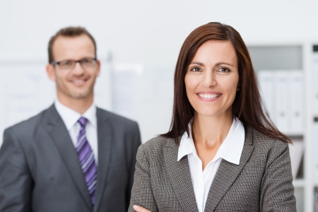 Beautiful smiling businesswoman standing with folded arms looking at the camera with a beaming friendly smile watched in the background by her male colleague