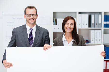Business team holding a blank white sign with a smiling successful man and woman standing side by side in the office with the sign in front of them with copyspace for your text or advertisement photo
