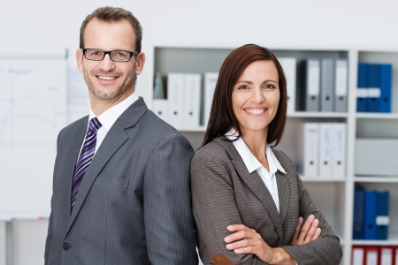 Professional business man and woman standing back to back in the office looking at the camera with confident smiles at the success of their partnership photo