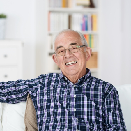 Happy senior man with a beaming smile wearing glasses sitting back relaxing in a chair at home photo