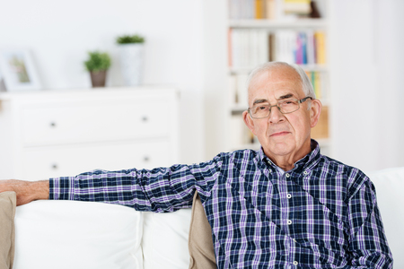 solitude: Thoughtful senior man at home sitting in a chair in the living room looking at the camera with a serious expression