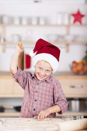 Laughing little boy baking Christmas cookies standing at the counter with the pastry cutters in his hand as he cuts the shapes from the pastry photo
