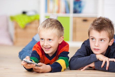 Happy young boy lying on his stomach on the floor with a friend or his brother using a remote control to change the program on the television photo