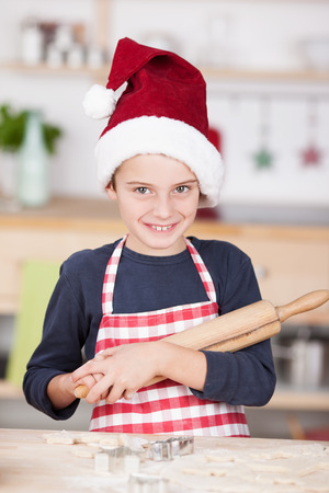 Cute young boy in a festive red Santa Hat and apron in the kitchen holding a wooden rolling pin in his hands as he stands over his pastry for cookies on the counter photo