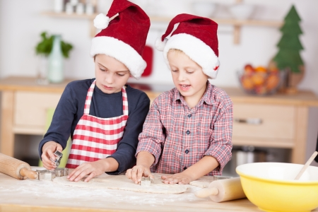 Two cute Caucasian boys wearing Santas hats and preparing Christmas cookies with shapes photo