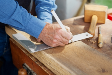square ruler: Closeup photo of a carpenter using scale and pencil to mark on the wood.