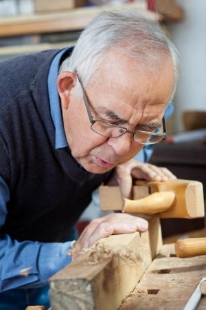 old plane: Senior man blowing shavings on wood at workshop