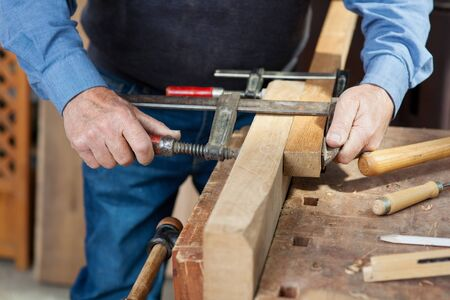rigidity: Image of a carpenter joining two pieces of wood using screw clamp in the workshop.