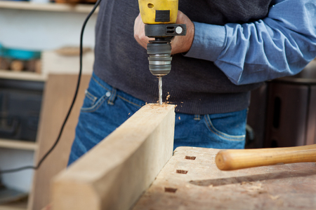 Midsection of senior male carpenter using electric drill at workbench photo