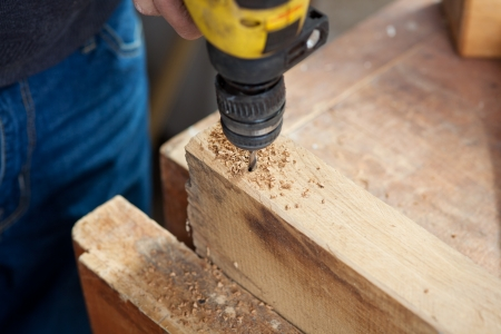 Image of a carpenter using the drilling machine on wood piece to make holes for screws. photo