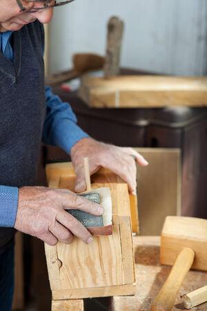 sanding block: Senior male carpenter using sandpaper for polishing birdhouse at worktable in workshop