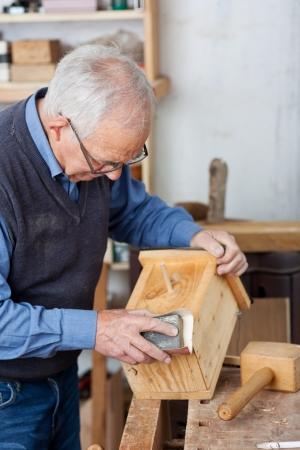 worktable: Senior male carpenter using sandpaper for polishing birdhouse at worktable in workshop
