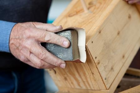 sanding block: Using sandpaper for polishing birdhouse at worktable in workshop