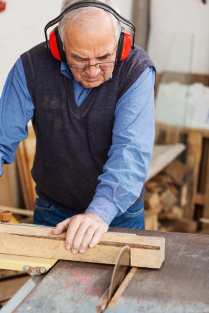woodworking: Senior man wearing red ear protectors while using table saw for cutting wood at workshop Stock Photo