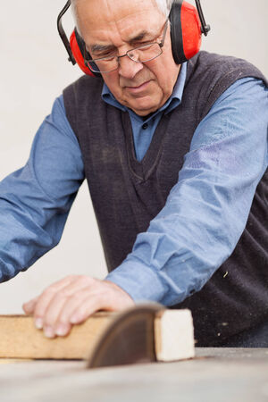 Senior man wearing ear protectors while using table saw for cutting wood at workshop photo