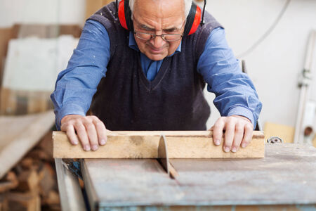 protectors: Senior man wearing ear protectors while using table saw for cutting wood at workbench Stock Photo