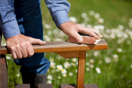 sanding block: Cropped image of carpenters hands polishing wood in park