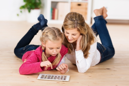 Attractive young mother and her cute little daughter lying on their stomachs on the floor playing with a tablet computer photo