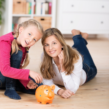 Attractive young mother teaching her little daughter to save as they lie on the floor together feeding coins into a piggy bank photo