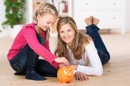 putting money in pocket: Happy little girl saving her pocket money sitting on the living room floor with her attractive young mother putting coins into the slot of a piggy bank