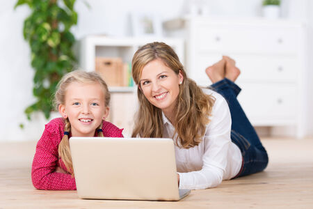 Sweet young girl with her mother lying together on the living room floor smiling at the camera as they work together on a laptop computer Stock Photo - 23487251