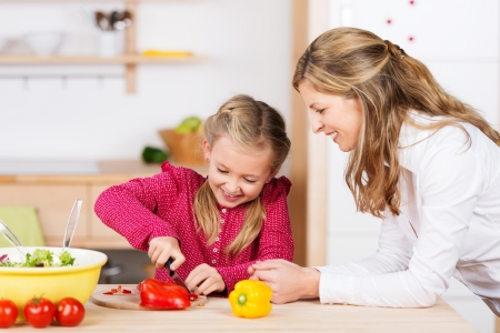 Mother watching her daughter prepare the meal as she leans on the counter with a happy smile while the little girl chops fresh vegetables photo