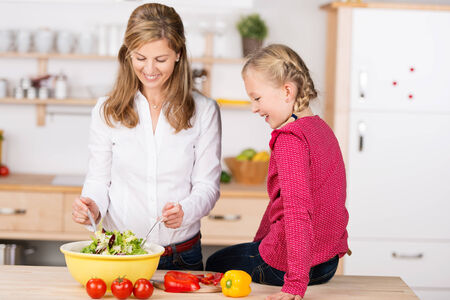 tosses: Smiling mother and daughter preparing a salad together in the kitchen as the little girl sits on the wooden counter top watching as Mum tosses the salad