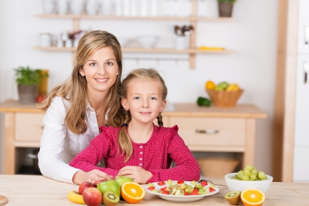 Beautiful little girl with her mother in the kitchen preparing a fresh fruit salad as the two pose side by side looking at the camera with charming friendly smiles photo