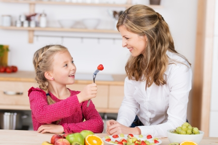 Adorable little girl feeding her mother a delicious ripe red strawberry as they have fun together in the kitchen preparing a fresh fruit salad photo