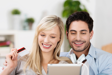 Happy online shoppers with an attractive young couple waving a credit card in the air as they browse the internet on a tablet-pc photo