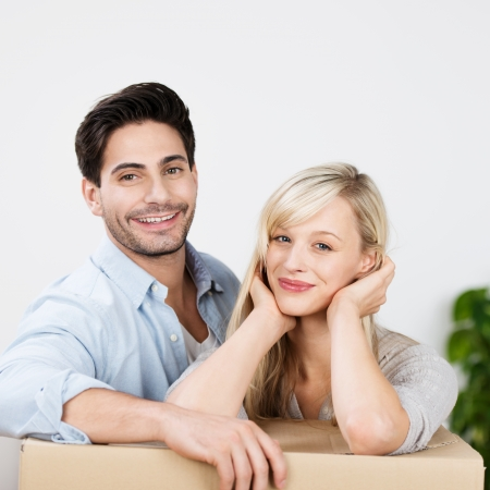 removals: Happy attractive young couple with a packing carton for house removals resting their elbows on the top and smiling in satisfaction at their new home