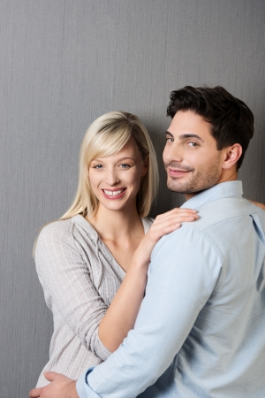 facing to camera: Smiling loving young couple standing facing each other in an affectionate embrace pausing to turn and smile at the camera against a grey studio background