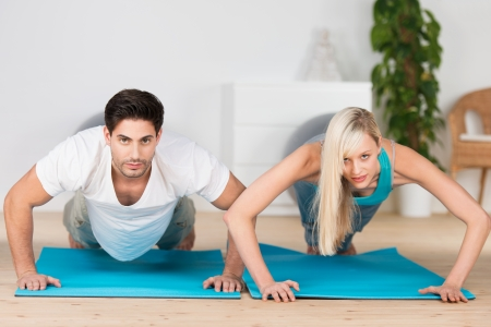 Young couple working out at the gym doing press ups on exercise mats looking up at the camera in the raised position photo