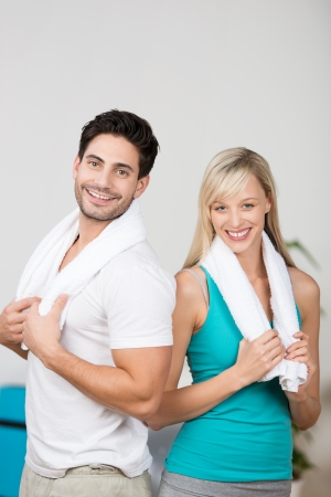Young couple relaxing after exercising standing close together with towels draped around their shoulders smiling at the camera photo