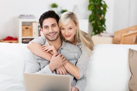 echtgenoot: Aanhankelijk paar ontspannen thuis met de man zittend op de bank met zijn laptop, terwijl zijn vrouw staat achter knuffelen hem met een glimlach