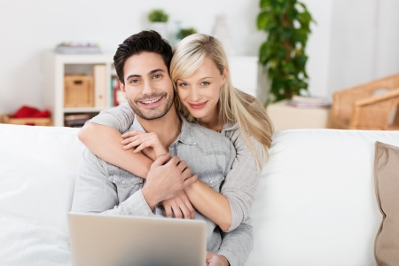 Affectionate couple relaxing at home with the husband sitting on the sofa with his laptop computer while his wife stands behind hugging him with a smile photo