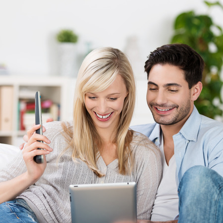 Smiling couple relaxing with a tablet computer reading information on the screen as they sit close together on the sofa at home photo