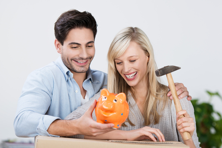 Laughing couple preparing to smash the piggy bank as they sit together on the sofa with the wife holding a raised hammer photo