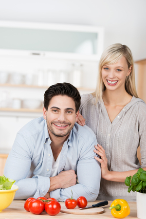 Young couple smiling as they prepare a healthy meal standing close together in the kitchen leaning on the counter laden with fresh ingredients Stock Photo - 23535369