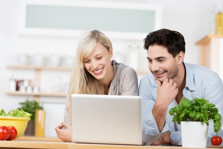 laptop stand: Young couple browsing the internet on a laptop computer as the stand together at the kitchen counter surrounded by fresh ingredients