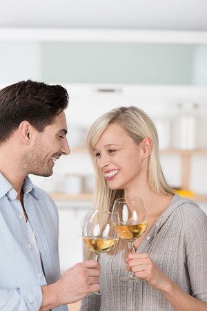 Laughing couple toasting each other with white wine clinking their glasses in celebration photo