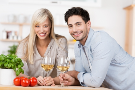 laden: Smiling happy couple drinking wine in the kitchen leaning on the counter laden with fresh ingredients for a healthy meal Stock Photo